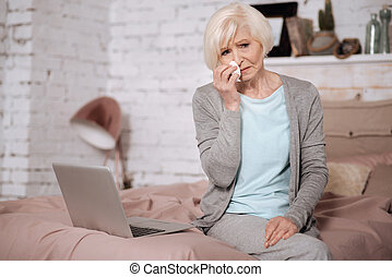 Aged woman crying while sitting on bed - Very bad news....