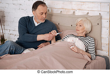 Senior man giving thermometer to his sick wife