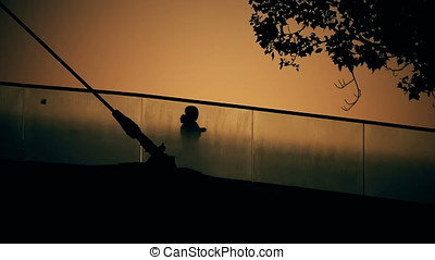 Back Lit Silhouette of Woman Crossing Bridge at Sunset -...