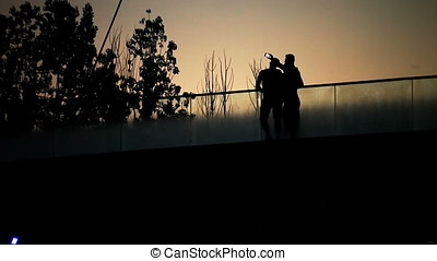 People Taking Selfie on Bridge at Sunset Back Lit Silhouette...