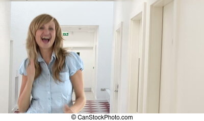 Young woman celebrating a good news in the school corridors...