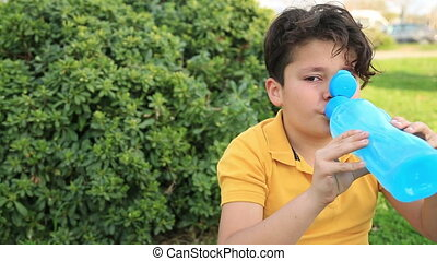 Child drinking water at the outdoor - Portrait of a cute...