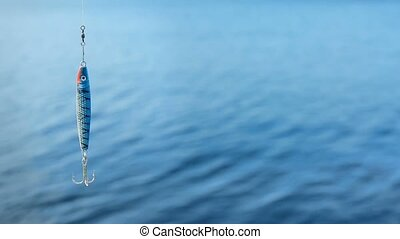 Minnow fluttering on fishing-line over sea background -...