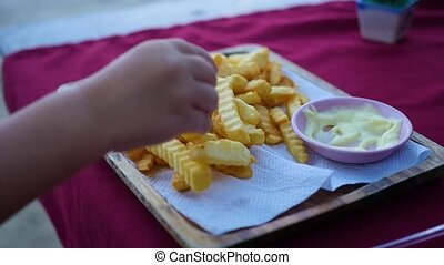 hand picks up the fried potatoes from the plate.