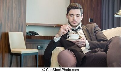 Concentrated serious businessman drinking coffee