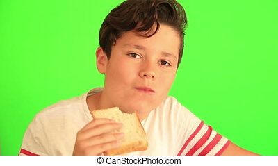 Child eating peanut butter sandwich - Boy eating a peanut...