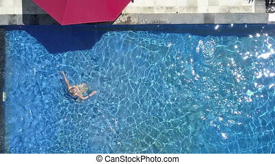 The young beautiful woman swims in the pool in a tropical...