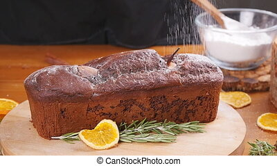 Sugar powder is poured onto the chocolate cake - Powder is...