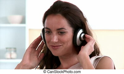 Radiant woman listening music in the living-room