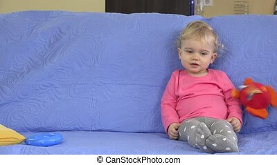 Soft toys rain falling on cute blond girl sitting on sofa....