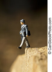 Walking off a cliff - Businessman figurine posed to look...