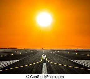 Airport runway with big sun in sunset light - Airport runway...