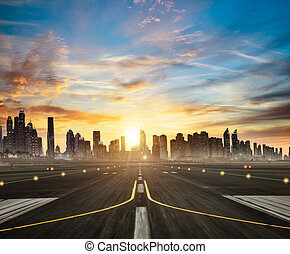 Airport runway with modern city on background in sunset...