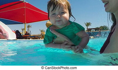 Baby girl swimming under water in mothers hands in swimming...