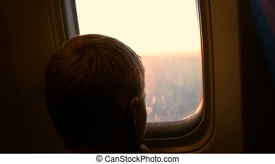 A child looking out the window of an airplane at sunset