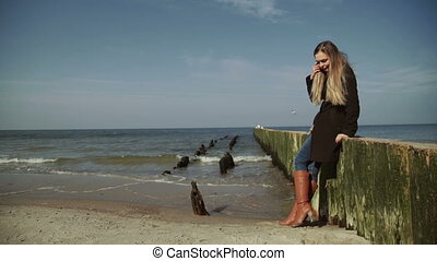 A woman Standing and walking on wooden breakwaters near the...