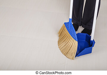 woman legs with broom and dustpan sweeping floor - woman...