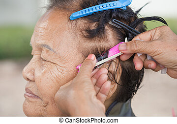 hand of a hairstylist doing a perm rolling hair of senior...