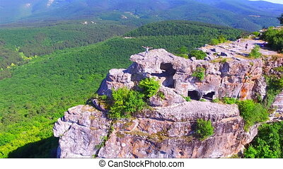 Aerial view on man standing alone on the big rock plateau