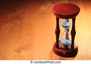 Old Hourglass - Vintage hourglass with blue sand standing on...