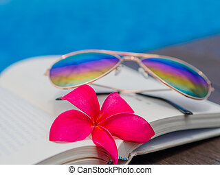 Book and sunglasses, blue water background,
