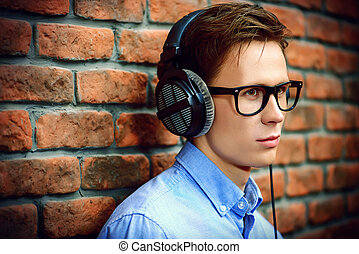 young melancholic man - Calm young man listens to music in...