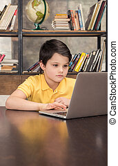 Concentrated schoolboy sitting at table and using laptop