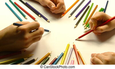 Close up of male and female hands drawing with colored pencils together