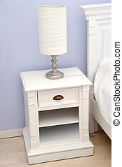 Bedside table with lamp - A white bedside table with a white...