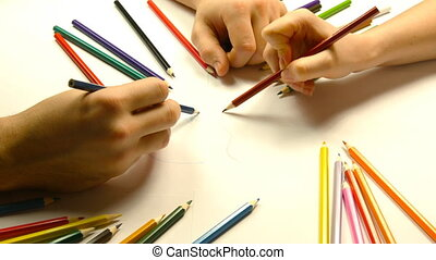 Close up of male and female hands drawing with colored...