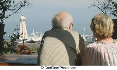 Seniors couple looking at the sea while sitting in the cafe on the street