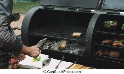Man prepares fish on the grill. Man takes fish from grill