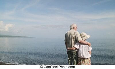 Older people standing by the sea