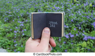 Spring sale concept, book with text and spring field with blue flowers
