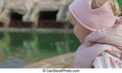 Little girl standing near the pond with the fishes outdoor