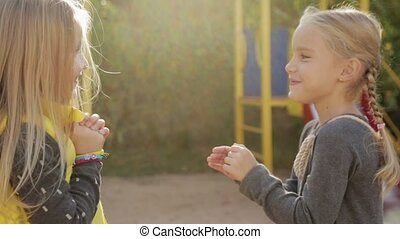 Two little girls preschoolers fooling around and playing patty-cake