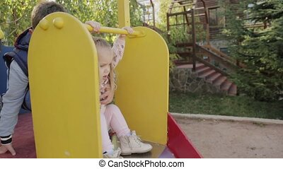 Little boy and girl roll down from the slide at the...