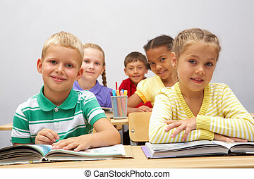 Diligent pupils - Portrait of smart pupils sitting in the...