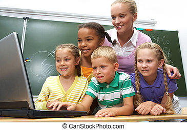 Education - Portrait of pupils looking at the laptop with...