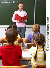 Lesson of literature - Rear view of pupils sitting at the...