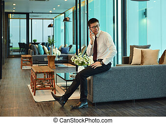 An Asian business man calling in business in a lounge of...