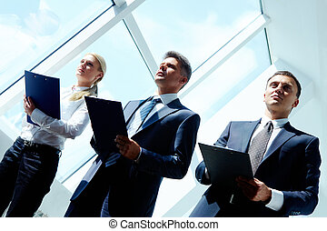 Conference work - Row of three smart employees listening to...