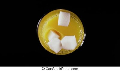 Sugar drops into a glass with juice. Top view. Slow motion -...