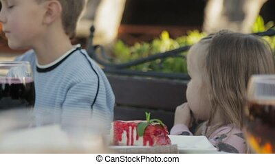 Little girl eating sauce from the cheesecake in the...