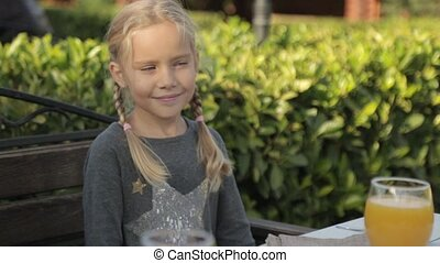 Little girl with two plaits sitting at the table
