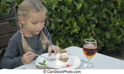 Cute little girl with pigtails eating dessert at the outdoor...