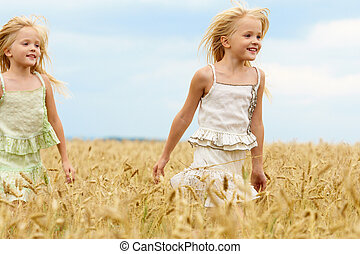 Carefree twins - Portrait of happy girl running down wheat...