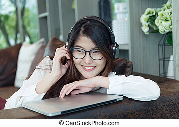 Asian girl listening to songs with laptop in living room, person