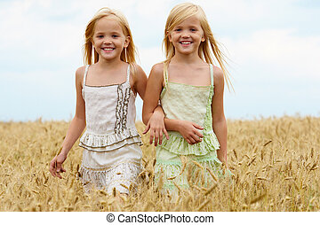 Walking together - Portrait of cute twins walking down wheat...