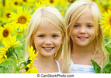 In sunflowers - Portrait of cute sisters in sunflower field